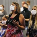 Parishioners sing during a service at Grace Bible Church on Sunday, May 24, 2020, in Tempe, Ariz. Parishioners practiced social distancing, most wearing face coverings, as the church held its first in-person service since March due to the coronavirus. (AP Photo/Ross D. Franklin)