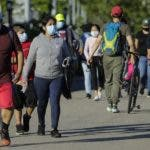 Pedestrians wear protective masks during the coronavirus pandemic as they enjoy warm weather in Flushing Meadows Corona Park, Tuesday, May 26, 2020, in the Queens borough of New York. (AP Photo/Frank Franklin II)