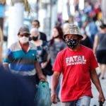 AME3064. SAO PAULO (BRASIL), 29/05/2020.- Personas con tapabocas caminan frente a tiendas cerradas por la situación del coronavirus este viernes en la ciudad de Sao Paulo (Brasil). La retracción del 1,5 % que la economía brasileña sufrió en el primer trimestre de 2020 aún sin sentir totalmente los efectos de la paralización de actividades por la pandemia del COVID-19 abortó el proceso de recuperación económica que el país intentaba desde 2017, admitió este viernes el Gobierno. EFE/Sebastião Moreira