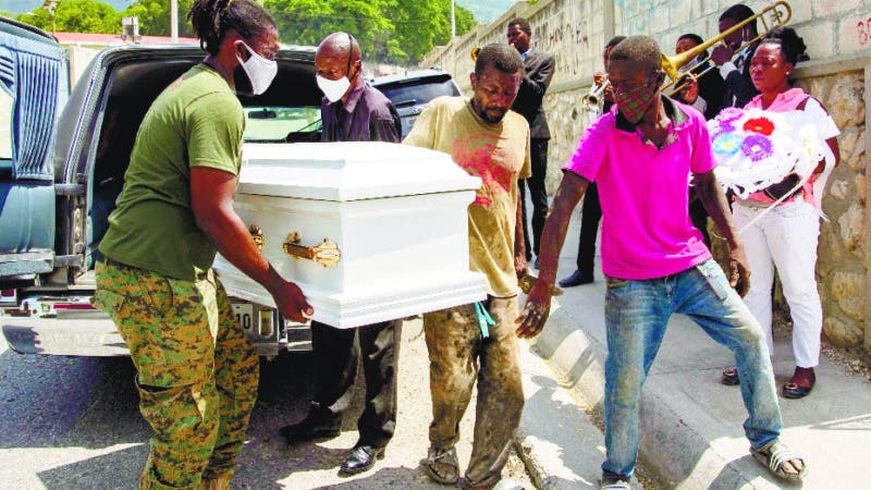 Cemetery workers carry the coffin with the body of 7-year-old Lovena Luberice to the Freres Public Cemetery in Port-au-Prince, Haiti, Wednesday, May 20, 2020. Lovena Luberice was one of 13 children and two adults that died during Feb. 13 fire at a Church of Bible Understanding home in the town of Kenscoff, Haiti. Her mother was waiting for justice and compensation from the Pennsylvania-based nonprofit group that ran the home before laying her to rest but could wait no longer. (AP Photo/Dieu Nalio Chery)