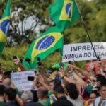 """BRA102. BRASÍLIA (BRASIL), 24/05/2020.- Simpatizantes del presidente de Brasil, Jair Bolsonaro, realizan una manifestación de apoyo al mandatario este domingo, en Brasilia (Brasil). En el letrero se lee: """"La prensa es enemiga de Brasil"""". Cientos de seguidores del presidente de Brasil, Jair Bolsonaro, se aglomeraron este domingo cerca del palacio de Gobierno para alabar a su ídolo, que sin protección se mezcló entre la multitud, ignorando de nuevo las recomendaciones por el COVID-19, una pandemia que no es prioridad para el mandatario. EFE/ Joédson Alves"""