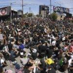 En esta imagen tomada con un gran angular, manifestantes sentados en un cruce durante una protesta por la muerte de George Floyd, un hombre negro que murió tras ser detenido por la policía en Minneapolis, el sábado 30 de mayo de 2020 en Los Ángeles. (AP Foto/Mark J. Terrill)