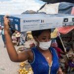 AME6592. PUERTO PRÍNCIPE (HAITÍ), 20/03/2020.- Una mujer con mascarilla camina este viernes en un mercado callejero en Puerto Príncipe (Haití). Haití registra los dos primeros contagios de coronavirus. El Gobierno introdujo las primeras medidas restrictivas, incluido el cierre de la frontera terrestre, el pasado domingo, para tratar de evitar la llegada del coronavirus al país, que tiene el sistema sanitario más frágil de América. EFE/Jean Marc Hervé Abelard