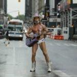 Robert Burck, el Naked Cowboy (Vaquero desnudo), posa para los fotógrafos en Times Square durante la pandemia de coronavirus en Nueva York, el sábado 23 de mayo de 2020. (AP Photo/Frank Franklin II)