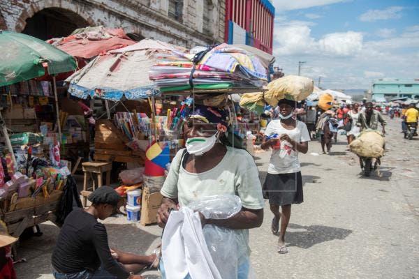 Una mujer con mascarilla camina en un mercado callejero en Puerto Príncipe (Haití). EFE