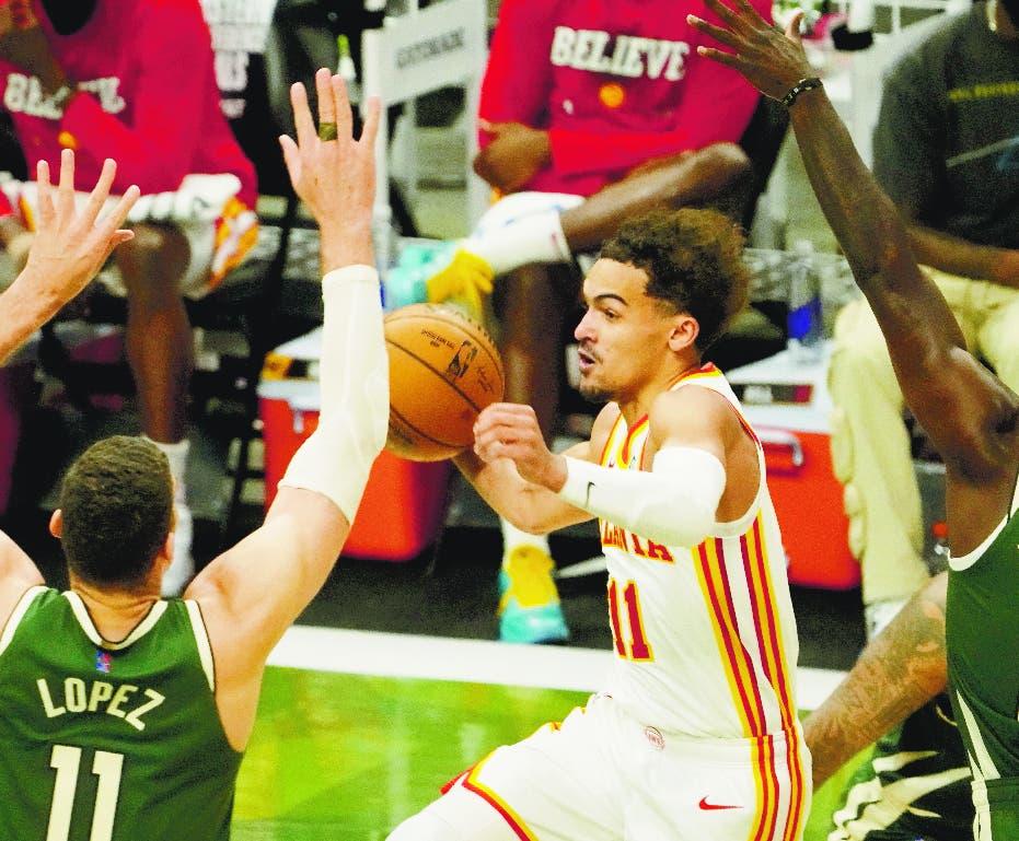 Trae Young, centro, driblea el balón ante Jrue Holiday y Brook Lopez.
