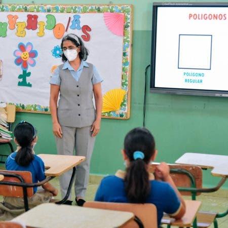 maestra y estudiantes en escuela para nuevo año escolar